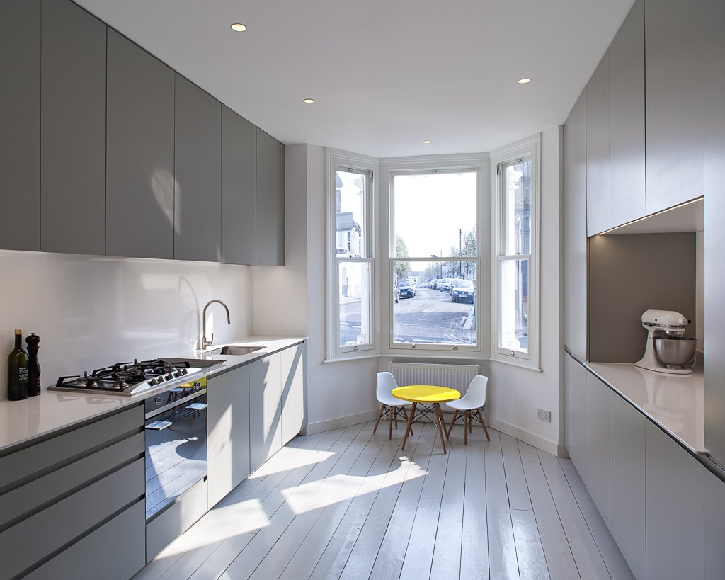 Throughout the home, the original strip-wood floorboards were preserved and painted a soft, muted gray. The cool tones of the kitchen are punctuated by a bright yellow children's table by the bay window. Tagged: Kitchen, Wood Cabinet, and Light Hardwood Floor.  Little Homes in London by Luke Hopping from A Compact, Light-Filled Victorian Renovation in England