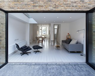10 Indoor-Outdoor Homes in London - Photo 3 of 10 - The large patio leads to a newly landscaped back garden. An expansive glass wall promotes seamless indoor-outdoor living. Inexpensive brick pavers were chosen for the rear patio; they offer textural contrast with the steel of the door, brick of the rear facade, and pale gray wood of the interior floors.