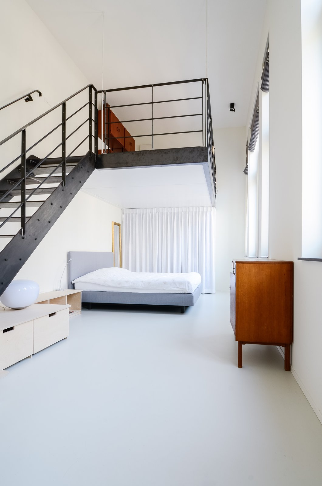 Once a teacher's lounge, the master bedroom now occupies the first-floor space. A hot rolled steel staircase leads to the lofted second-floor, an addition which brought more livable square footage to the overall program.  Bedrooms by Dwell from The Schoolhouse