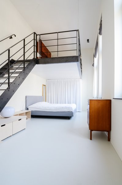 Once a teacher's lounge, the master bedroom now occupies the first-floor space. A hot rolled steel staircase leads to the lofted second-floor, an addition which brought more livable square footage to the overall program. Photo 3 of The Schoolhouse modern home