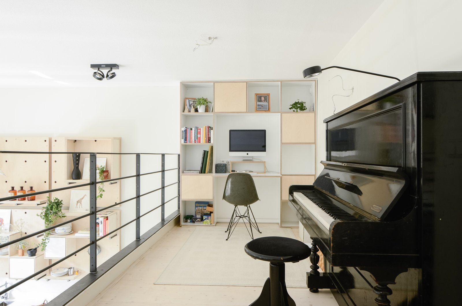 The loft addition afforded space for a home office and music area. The family chose to forego a dedicated office upstairs, instead prioritizing private bedrooms for each of the children. Shelving and a built-in desk anchor the loft's far wall. The Schoolhouse by Sarah Akkoush