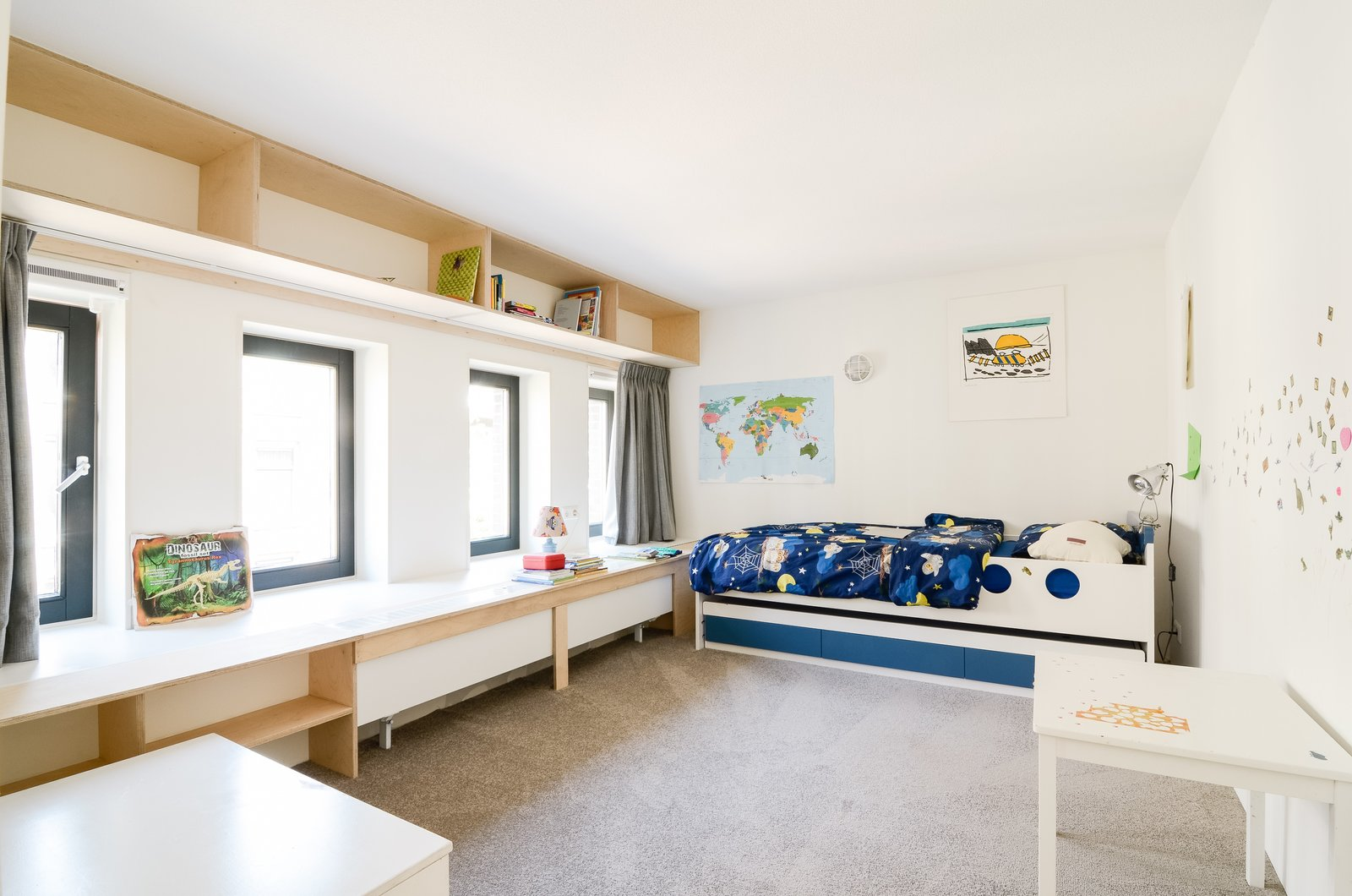 Another former teacher's lounge was converted into a kid's bedroom. For consistency, simple plywood, lightly coated with lacquer, was used for custom furniture and shelving.  The Schoolhouse by Sarah Akkoush