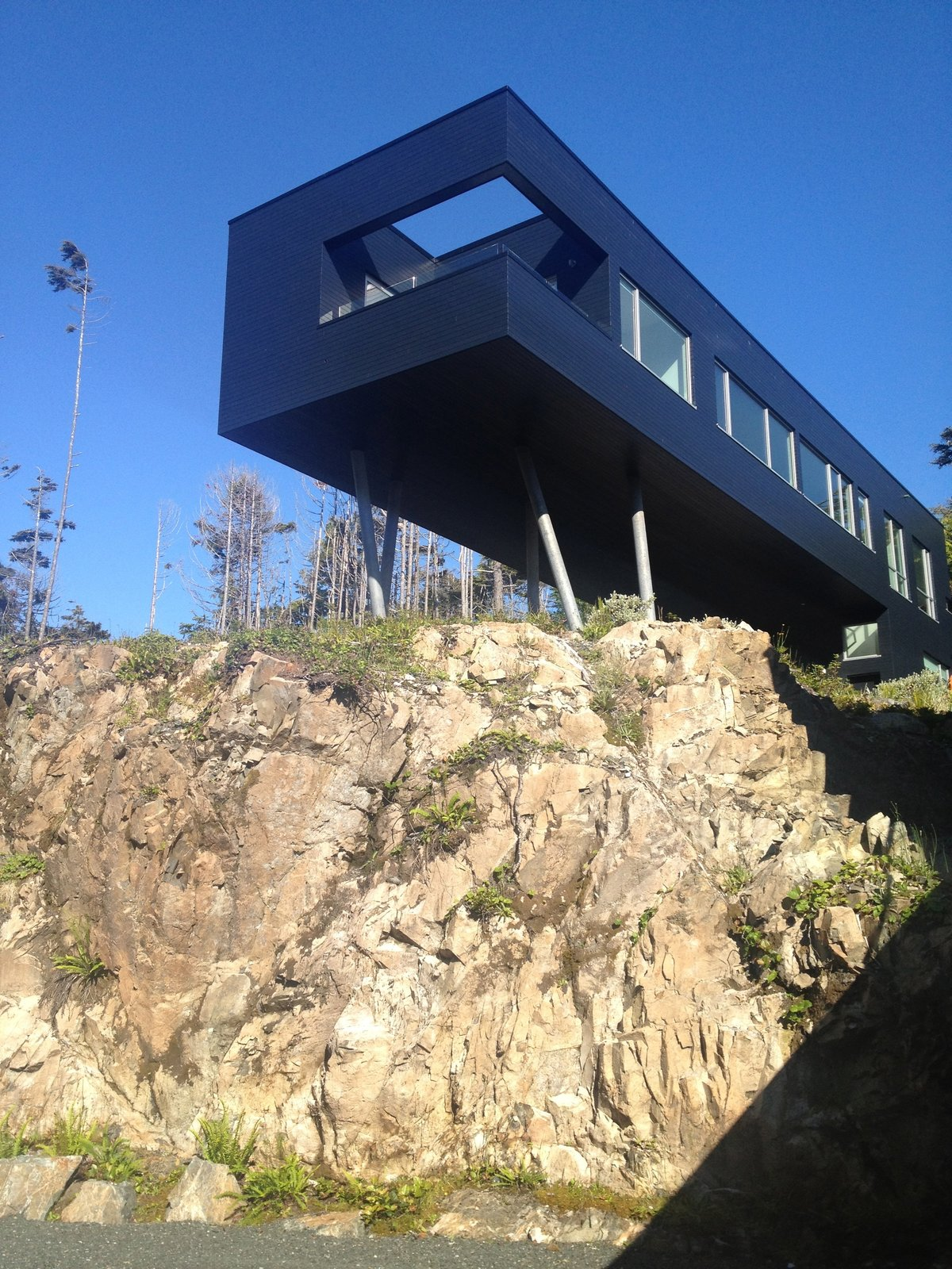 The L-shaped secondary building perches over a craggy escarpment. It offers the best vantage point for taking in the moss-planted roof, forest, and ocean.  Prefab by Low Junjie from A Giant, 20-Module Prefab Perched Across a Coastal Site in British Columbia