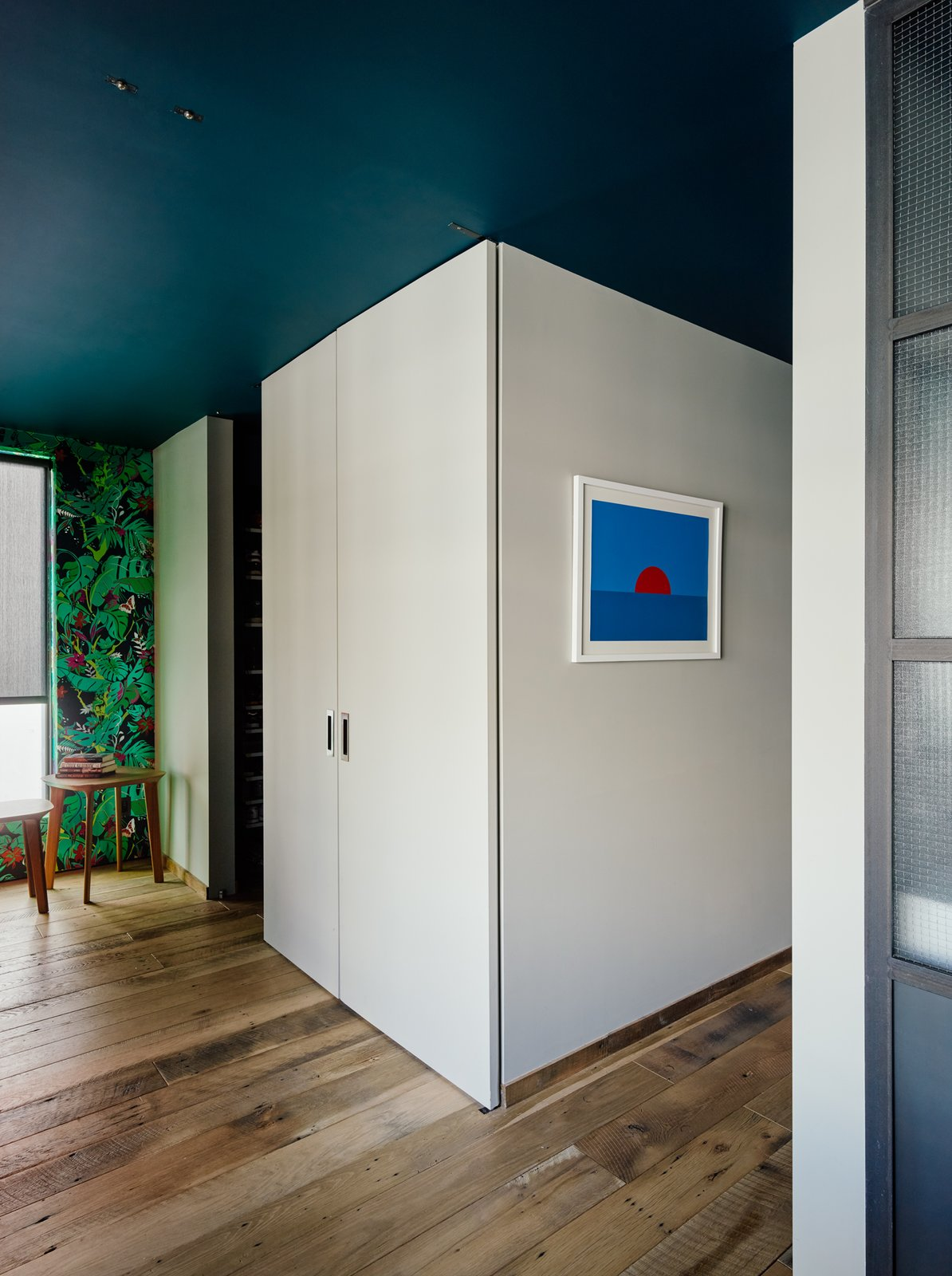 A system of full-height panel doors rotate in the space, closing off the bedroom and walk-in closet from the home office—a key feature for the residents, who often work from home.