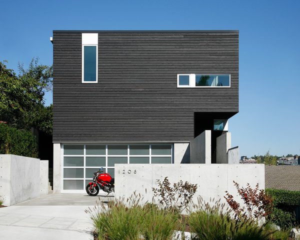 """""""The house turns its back to the street while opening up to the views to the northeast through a large glazed corner window system,"""" Hutchison says. One-by-four and one-by-six inch cedar siding, which were pre-stained in Cabot Semi-Transparent Black, were placed vertically and horizontally on the exterior as a subtle detail. Photo  of Portage Bay Bungalow modern home"""