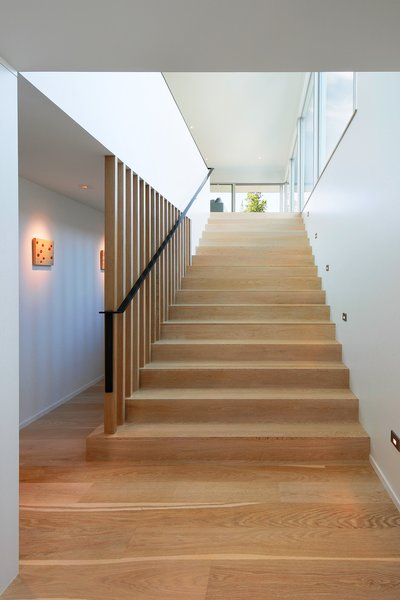 Custom bleached-white oak flooring covers the floors, including on the staircase to the property's second floor. Juno five-inch LED recessed wall lighting illuminates the steps at night. Photo 6 of Portage Bay Bungalow modern home