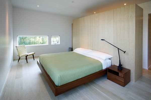 A Risom Lounge Chair by Knoll faces a BoConcept bed. A Tizio desk lamp from Design Within Reach acts as additional lighting. Custom casework by Hutchison and Allbee matches the kitchen's finished look. Photo 7 of Portage Bay Bungalow modern home