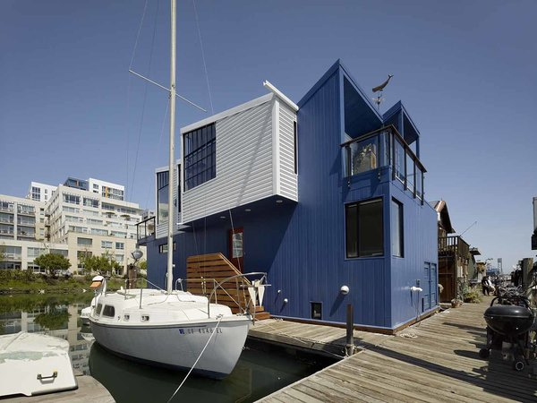 """Marked by its sawtooth roof and shipping container–like facade, the home is moored to the dock alongside boats. Since there's no way to paint a floating house, Nebolon chose to clad the exterior in 24-gauge metal siding coated with a fluorocarbon finish that will resist fading and chalking for 40 years. """"It's a very durable paint system that doesn't require periodic painting,"""" he explains. """"An annual hose-down will work just fine."""""""