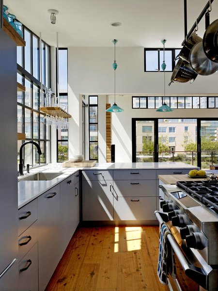 The kitchen is marked by its Wolf gas range, white Carrara marble countertop bar, and Cobb Rise & Fall pendants by Original BTC. The architect designed a custom wine glass holder, which hangs nearby.