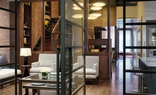 """A Warm, Luxurious New York City Duplex With a Dramatic Catwalk - Photo 1 of 7 - SPAN balanced the owner's passion for Arts and Crafts architecture with an """"unabashedly urban"""" sensibility, encapsulated by the exposed brick wall. Impressed with the results, the client tasked the firm with designing his Maine hideaway along similar aesthetic lines. The kitchen banquet is custom by SPAN."""