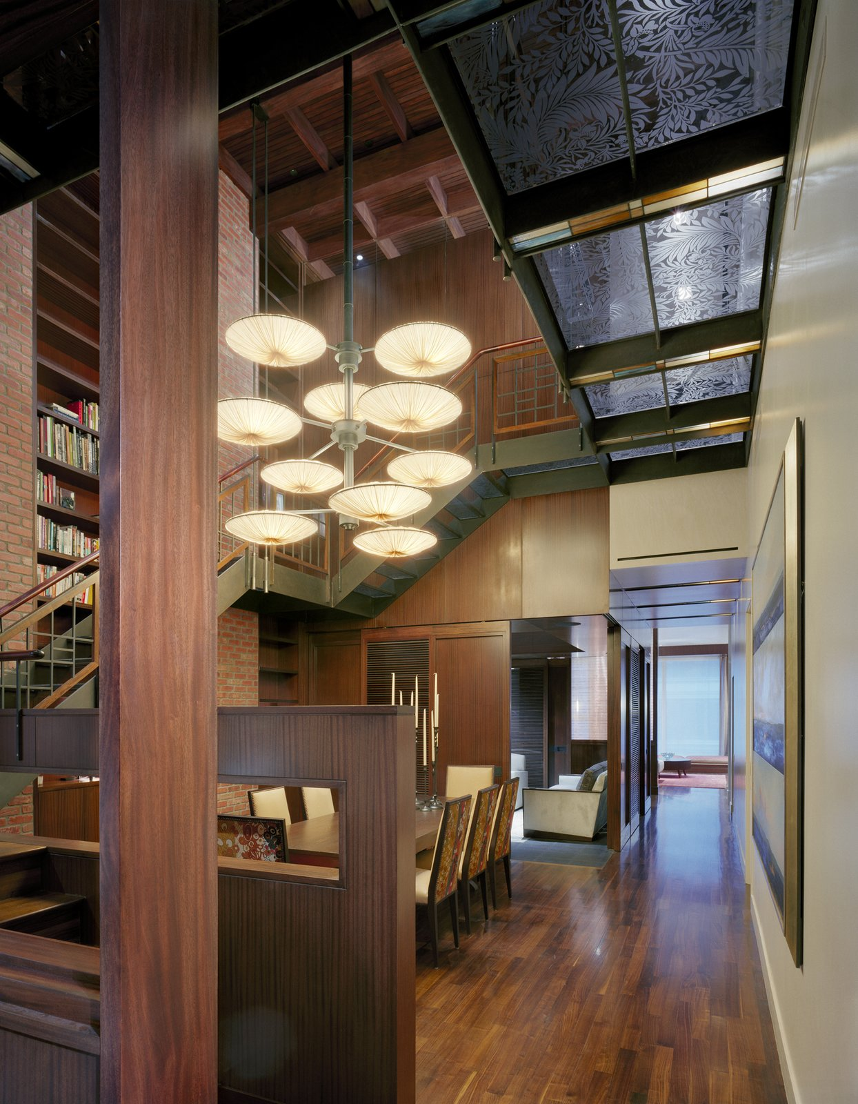 An enormous Bocci chandelier was mounted in a custom arrangement that takes advantage of the  atrium's vertical openness.  Nice homes + furniture by Goard Design Studio from A Warm, Luxurious New York City Duplex with a Dramatic Catwalk