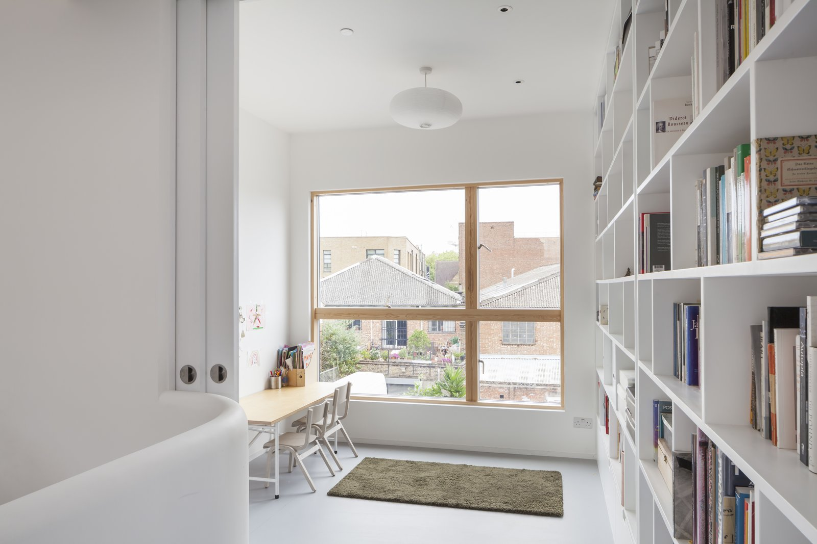 An office nook and library can participate in the open plan or disappear behind pocket doors. Tagged: Office, Shelves, and Bookcase.  Photo 4 of 7 in A Clever Sunken Roof Fills a London Terrace House with Light