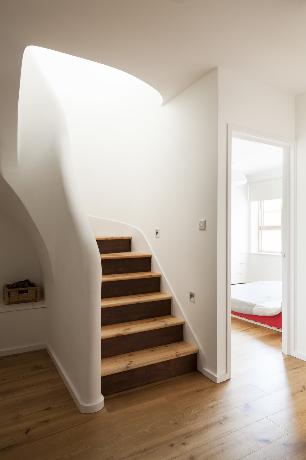The central staircase is a key element of the scheme. With the bedrooms and bathroom located on the entrance level, it was crucial to create an intuitive and inviting flow up toward the more social areas. On the upper floor, the central staircase divides and defines an otherwise open plan.