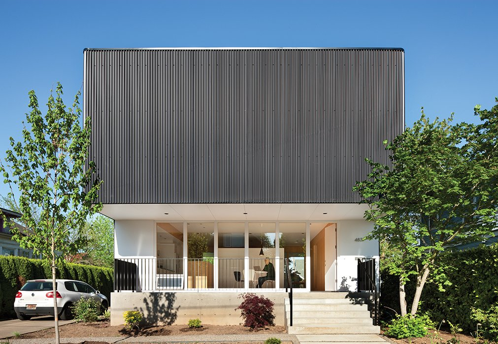 A cantilevered second floor addition wrapped in black corrugated steel gives Nick Oakley's home in the Alberta district of Portland an industrial feel from the outside, one that is countered by the welcoming, wood-dominated interior.  Modern Spaces in the Pacific Northwest by William Lamb from Modern Houses in Portland