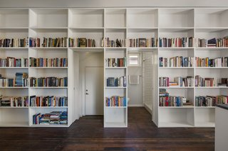 10 Ways to Solve Storage Problems in Small Spaces - Photo 7 of 10 - If you're a collector, find a way to highlight your passion without impeding on space. In this example, the residents' book collection resides in a wall of built-in shelving running the length of the room. The additional thickness of the bookshelves and the books provide acoustic separation between the hustle and bustle of the kitchen and the bedrooms.