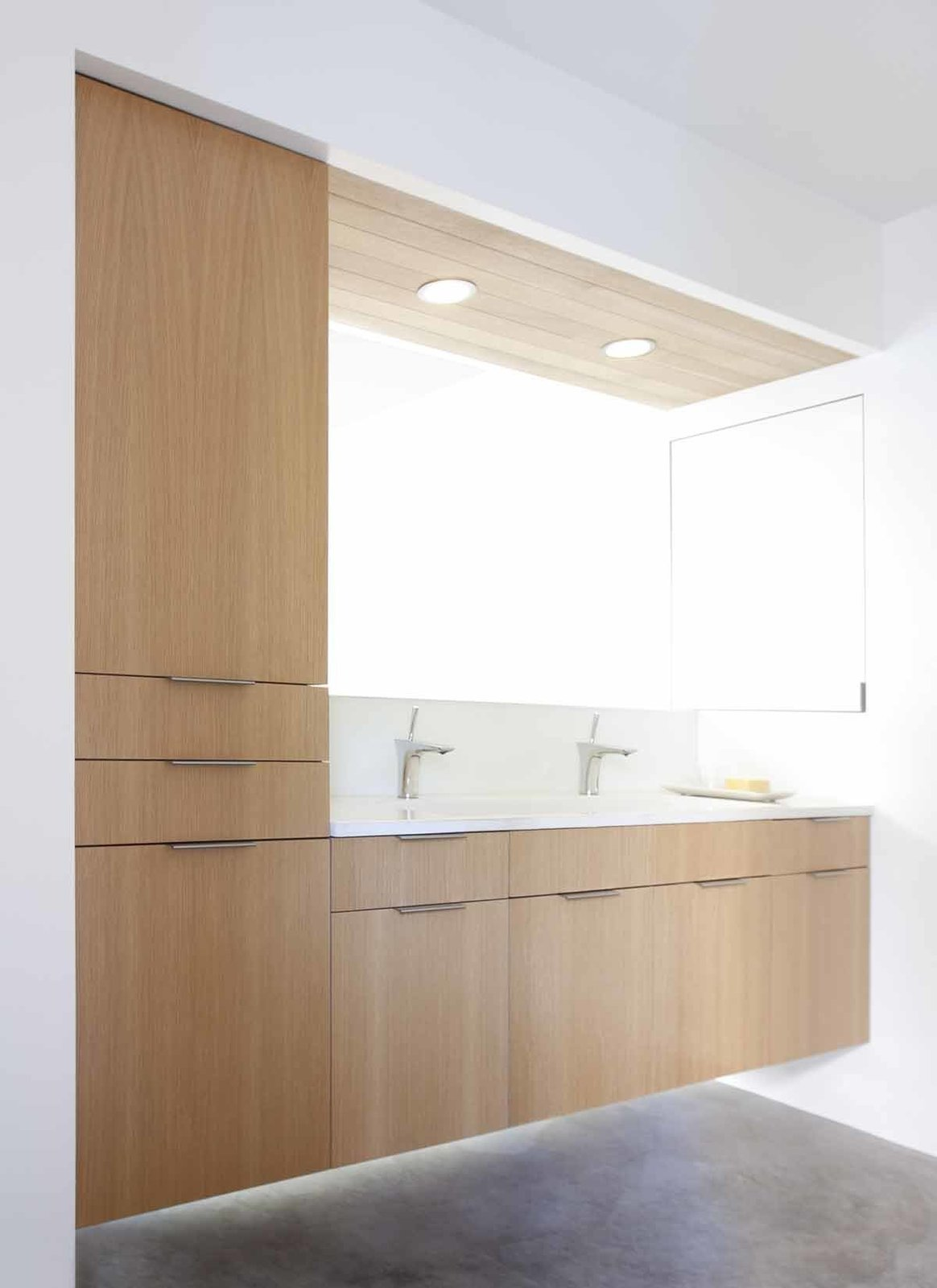 "The owners, who describe their design aesthetic as ""comfortable minimalism,"" envisioned a space with ""clean lines, simple materials, and straightforward methods,"" an vision shared by Franz and Seth Paré-Mayer. The new master bathroom features custom, locally built rift cut white oak cabinetry, consistent with many of the other spaces on the renovated level. The bathroom vanity floats above polished concrete floors. A bold cutaway was chosen in lieu of an anchoring wall. Unique fold-out mirrors lay flush against the side wall and cabinet when not in use, and swing towards the open center when needed. A custom cast concrete sink by It's Concrete, Hansgrohe Puravida faucet, and Heath Ceramics soap dish complete the space.  KS Mission by Sarah Akkoush"