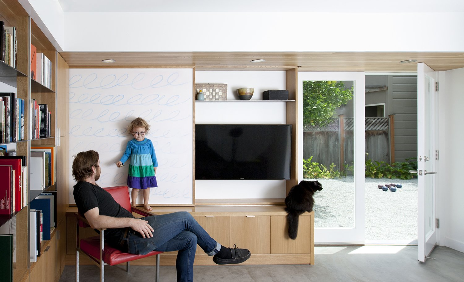 "The sliding wall panel is seen in its open position. In addition to several design elements serving multiple functions, great care was taken to develop a compelling design within the constraints of existing conditions. The remodel was confined to the existing building envelope, leaving the original footprint unchanged, but adding about 650 square feet of habitable space in the process. ""The plans,"" explains Paré-Mayer, ""respected existing structural conditions where possible to save on cost."" The finished concrete floor is, in fact, the structural slab, an efficient choice from a cost and materials perspective. The existing footings, which were wider than the framed interior walls, were kept intact in their original condition and location. The team was able to cleverly design around them by building usable closed storage to conceal the protruding foundation, as seen at the base of the media built-in."