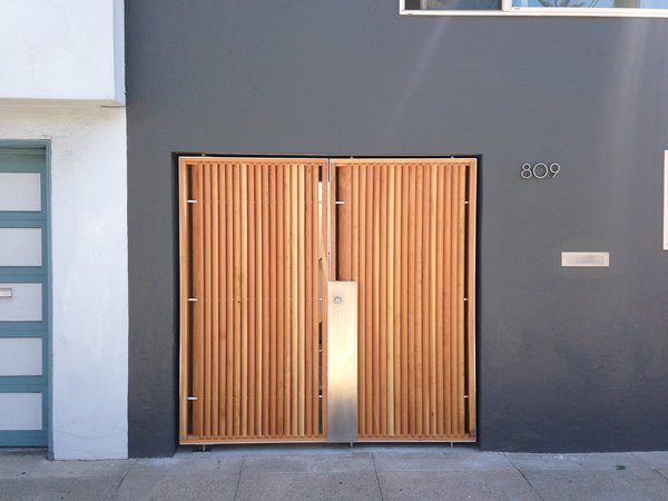 The focal point of the home's modernized exterior is a custom wood-and-steel entry gate designed by atelier KS and built by DeFauw Design + Fabrication, a local fabricator who also made custom closing hardware for the piece. Franz and Paré-Mayer paired angled cypress slats with an industrial metal frame to create the entryway. A few paces behind the gate, a large glass door provides direct access to the home, fulfilling the owners' wish for an entry vestibule that would be separate from the street. The angled wood slats offer privacy from the exterior, while selectively allowing light to penetrate through. Photo 10 of KS Mission modern home