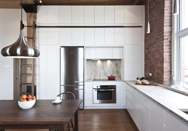 A floor-to-ceiling wall unit accommodates a fridge, stove, oven, and convertible custom cabinetry. The pendant light is from the Multi Luminaire showroom in Pointe Claire, Quebec; the appliances are from Bosch and Miele. Photo  of Brick House modern home