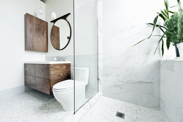 """What could I have that would feel luxurious, would make me feel really great?"" muses one of the homeowners. ""My husband and I travel a lot in Europe, and we always loved the marble showers. So we put a marble shower up against the window."" The sink and countertop are from Batimat, while the wall-hung vanity is another custom piece by Gepetto. Photo 5 of Brick House modern home"