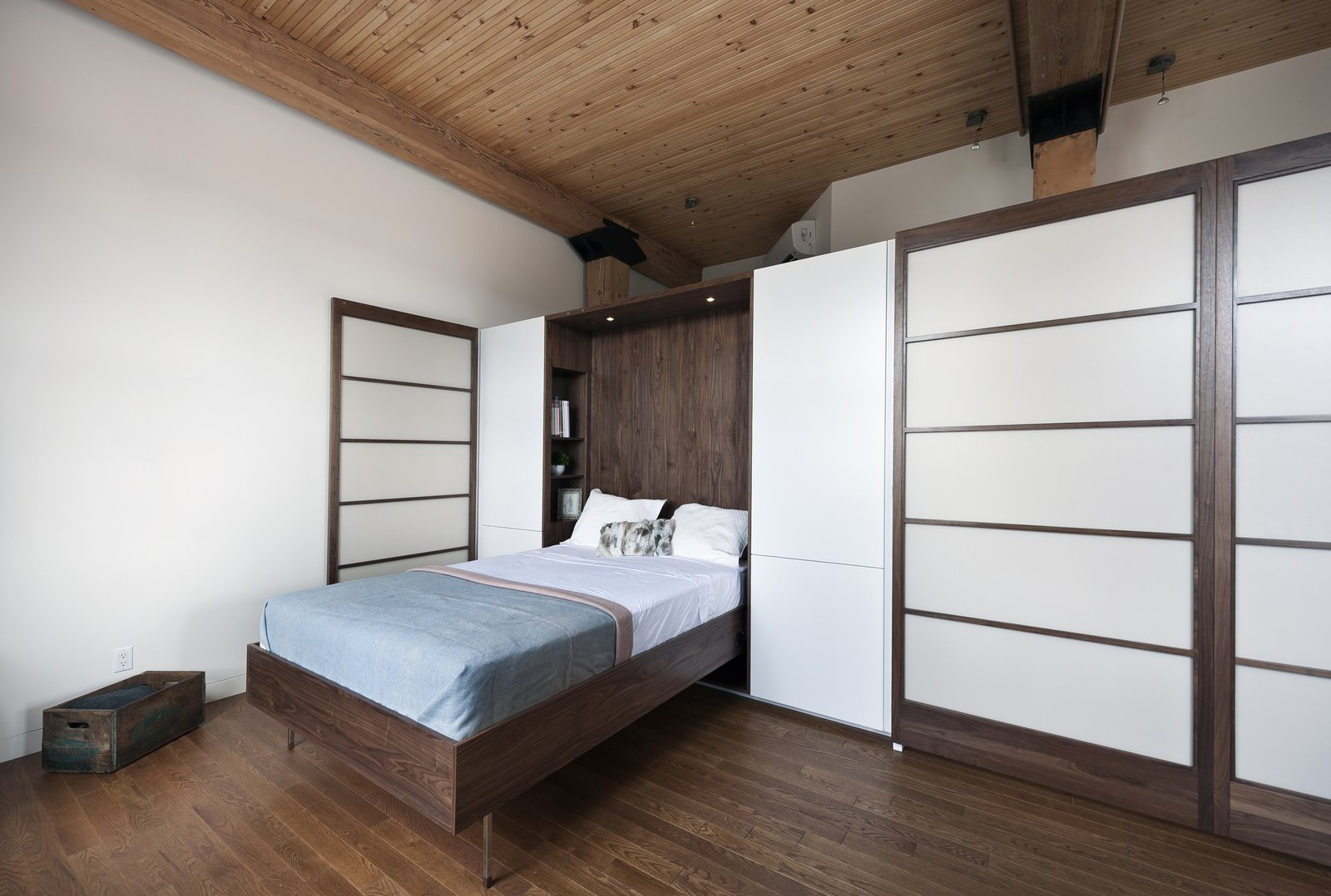 Gepetto built a Murphy bed that folds into a larger walnut storage unit. The wall, which also conceals a washer and dryer, does double duty as a partition between the bedroom and the loft's entrance.