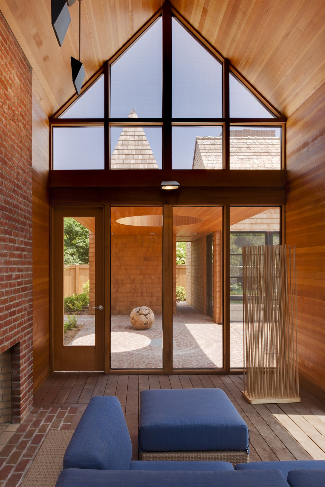 A Douglas fir ceiling in the screened porch and red bricks are accented by blue Arizona modular outdoor seating by Barlow Tyrie.  Desert Homes by Heather Corcoran from A Traditional Facade Hides A Light-Filled Modern Delaware Renovation