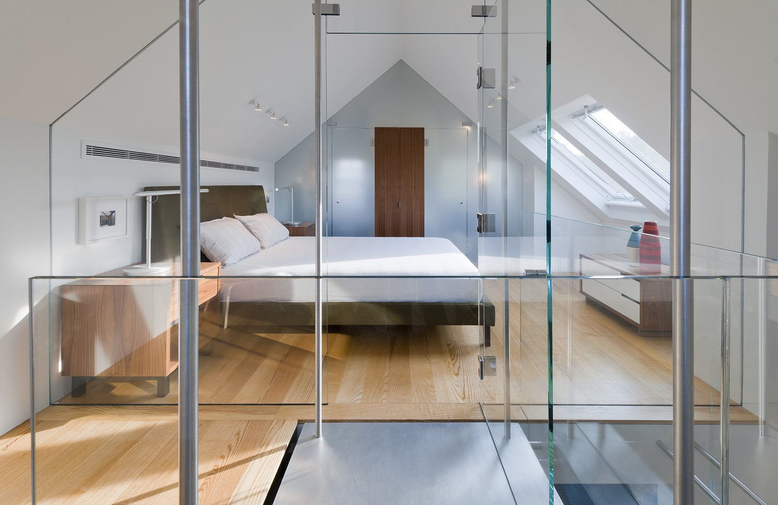"This custom glass structure by Ilex Construction allows for an abundance of light during the day. At night, Lightolier fixtures on the ceiling illuminate the Ella bed. Sherwin-Williams ""Pure White"" was painted on all interior walls. Bedrooms by Dwell"