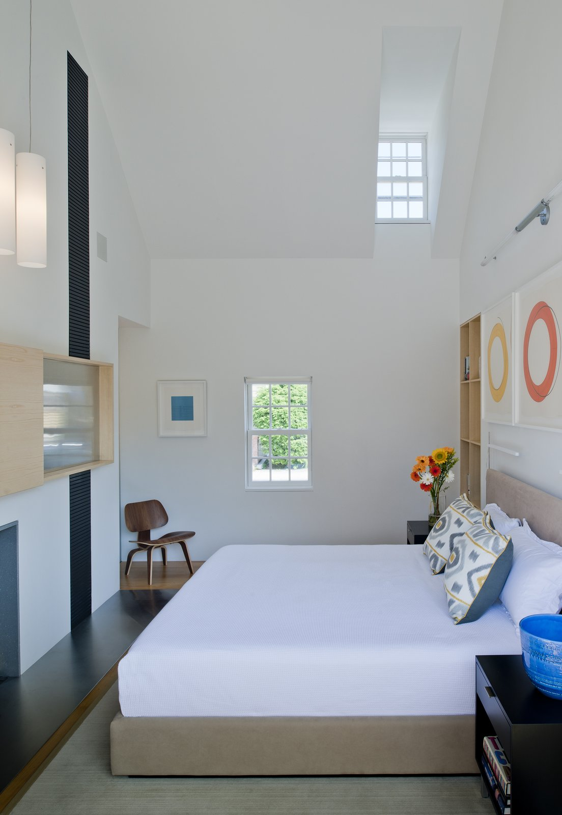 """In this project, the interior walls and ceilings in the existing historical component are white, and the walls and ceiling materials in the new pavilions are wood,"" Gurney said. In the master bedroom, a custom bed and nightstands by Baron Gurney Interiors sit across from an Eames molded plywood lounge chair.  Bedrooms by Dwell from A Traditional Facade Hides A Light-Filled Modern Delaware Renovation"