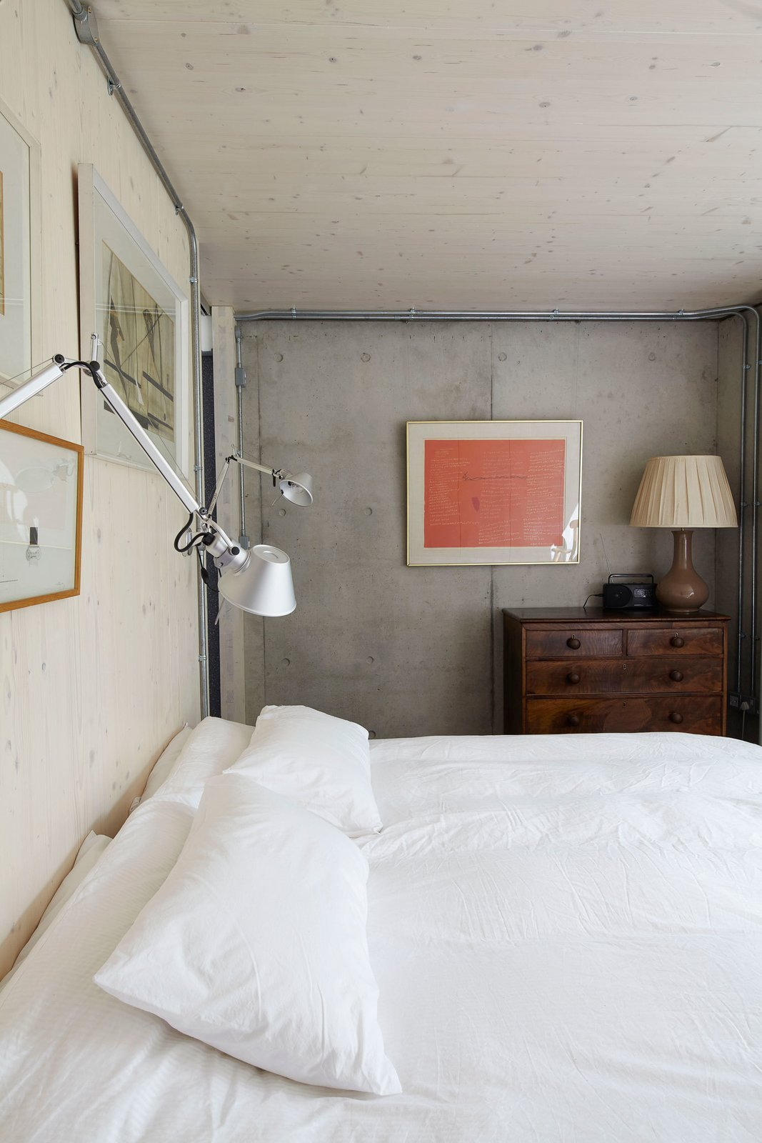 The lower level has a reinforced concrete frame. The timber and concrete surfaces are left exposed throughout the home. Tolomeo lights from Artemide hang above one of the beds.  Concrete by Jason Wong from Small But Mighty Passive House in London