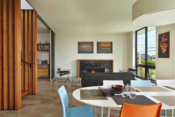 On the first level, the living room and dining room connect to a southeast-facing terrace, which catches the morning and midday sun. A pair of larch sliding doors join the two rooms. Two Marcel Breuer Wassily chairs from Knoll flank the rug, from Room & Board, and Portland Willamette Ovation II fireplace.