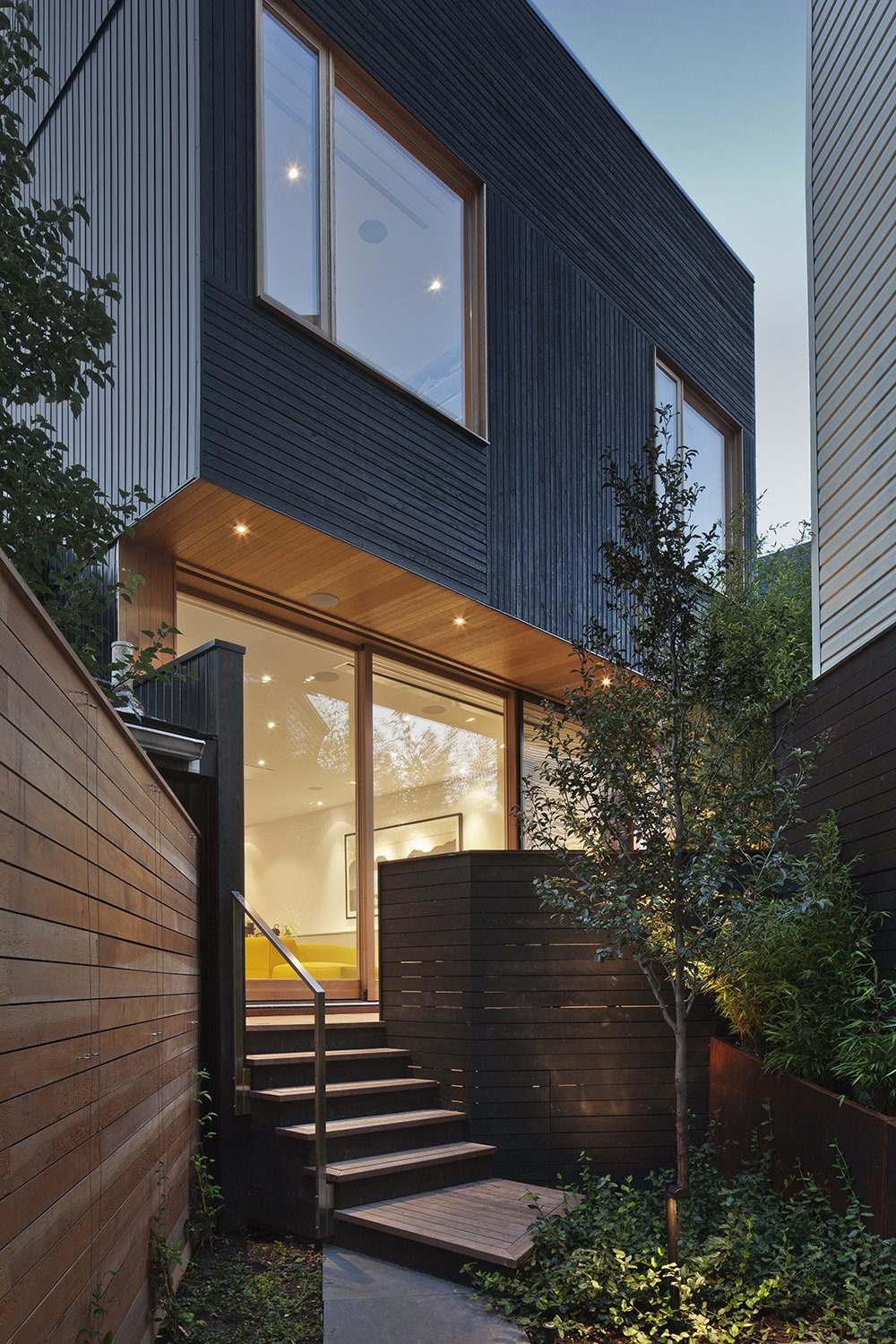 """The black siding is contemporary, but the texture of the wood grain is friendly and complements more traditional neighboring houses,"" Clarkson said. Windows are fabricated with Douglas fir. Ipe and stained black cedar make up the home's various decks.  King West by Kelly Dawson"
