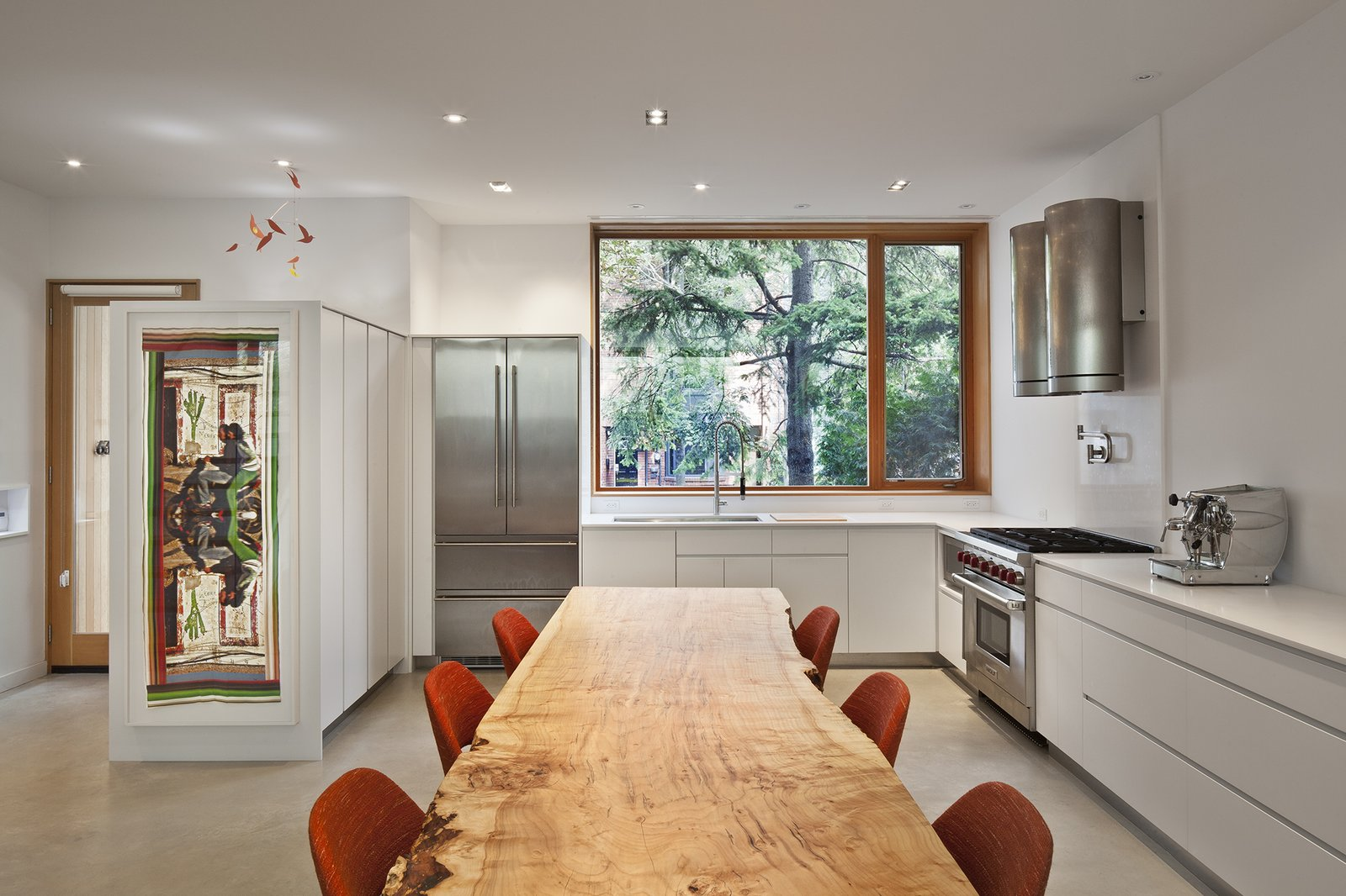 A 13-foot long dining table comprised of silver maple from Urban Tree Salvage is colorfully framed by Saarinen Executive side chairs. Over in the kitchen, a Liebherr refrigerator matches a Wolf stove.  King West by Kelly Dawson
