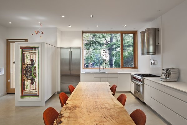 A 13-foot long dining table comprised of silver maple from Urban Tree Salvage is colorfully framed by Saarinen Executive side chairs. Over in the kitchen, a Liebherr refrigerator matches a Wolf stove. Photo 2 of King West modern home