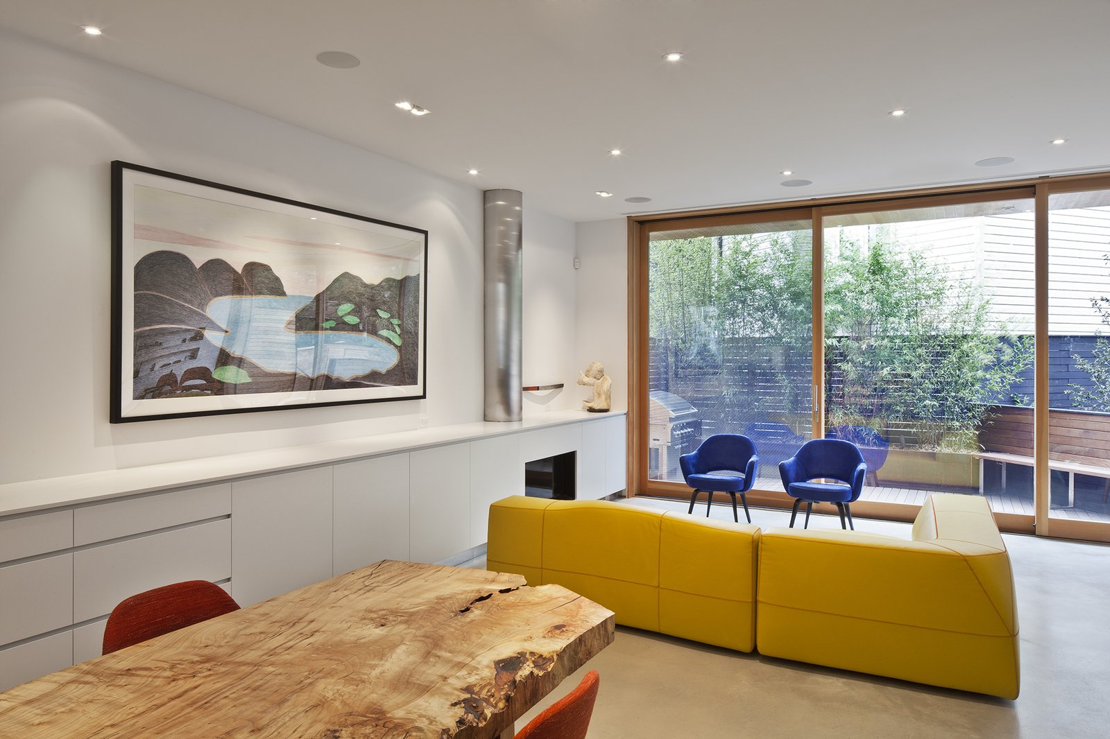 """""""The [design] is simple and flexible, with an open plan on the first floor that allows the kitchen to flow into the dining and living spaces,"""" Clarkson said. Concrete floors help to unify the spaces, which feature a B&B Italia Bend-Sofa and Saarinen executive armchairs in royal blue velvet."""