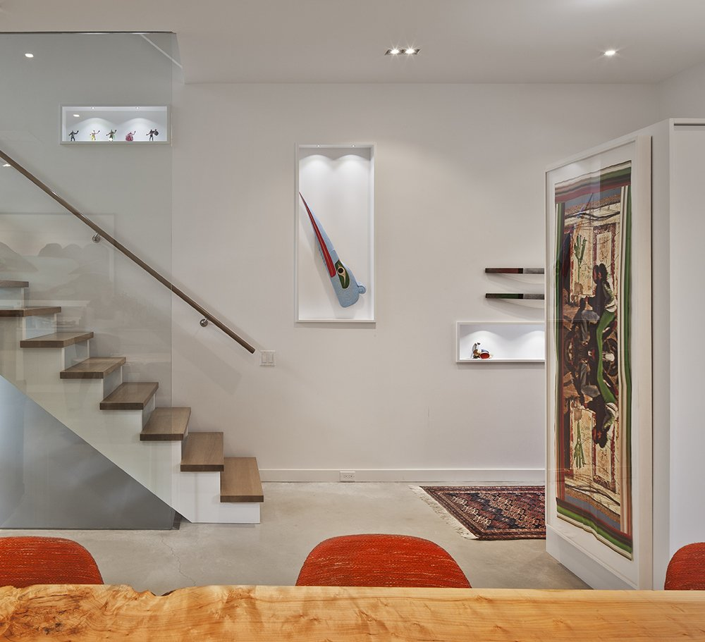 A custom glass structure supplied by Reale Born Inc. borders the stairs, which are made of solid white oak.  King West by Kelly Dawson