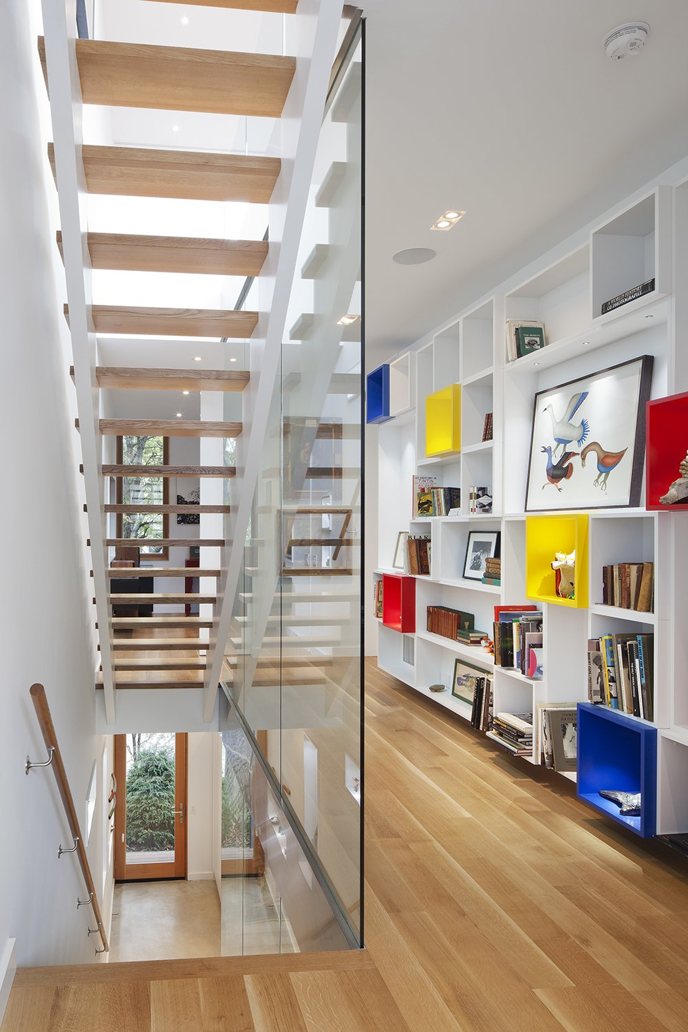"""The interior was designed as a backdrop to the art and life of its inhabitants,"" Clarkson noted. ""A custom-built wall of display cubes adds an accent of primary color in the second floor hallway."" Solid white oak flooring continues onto the second level from the stairs, and Middlebrook Woodworking Ltd. lacquered that same material for the display cubes."