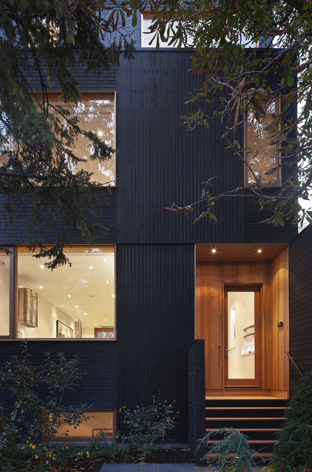 """""""The house is a three-story volume, but in order to minimize the reading of this volume from the street, we set the walls of the third floor back from the front and rear walls of the building,"""" Clarkson said. Black wood v-joint siding foils Douglas fir wood cladding around the door.  King West by Kelly Dawson"""