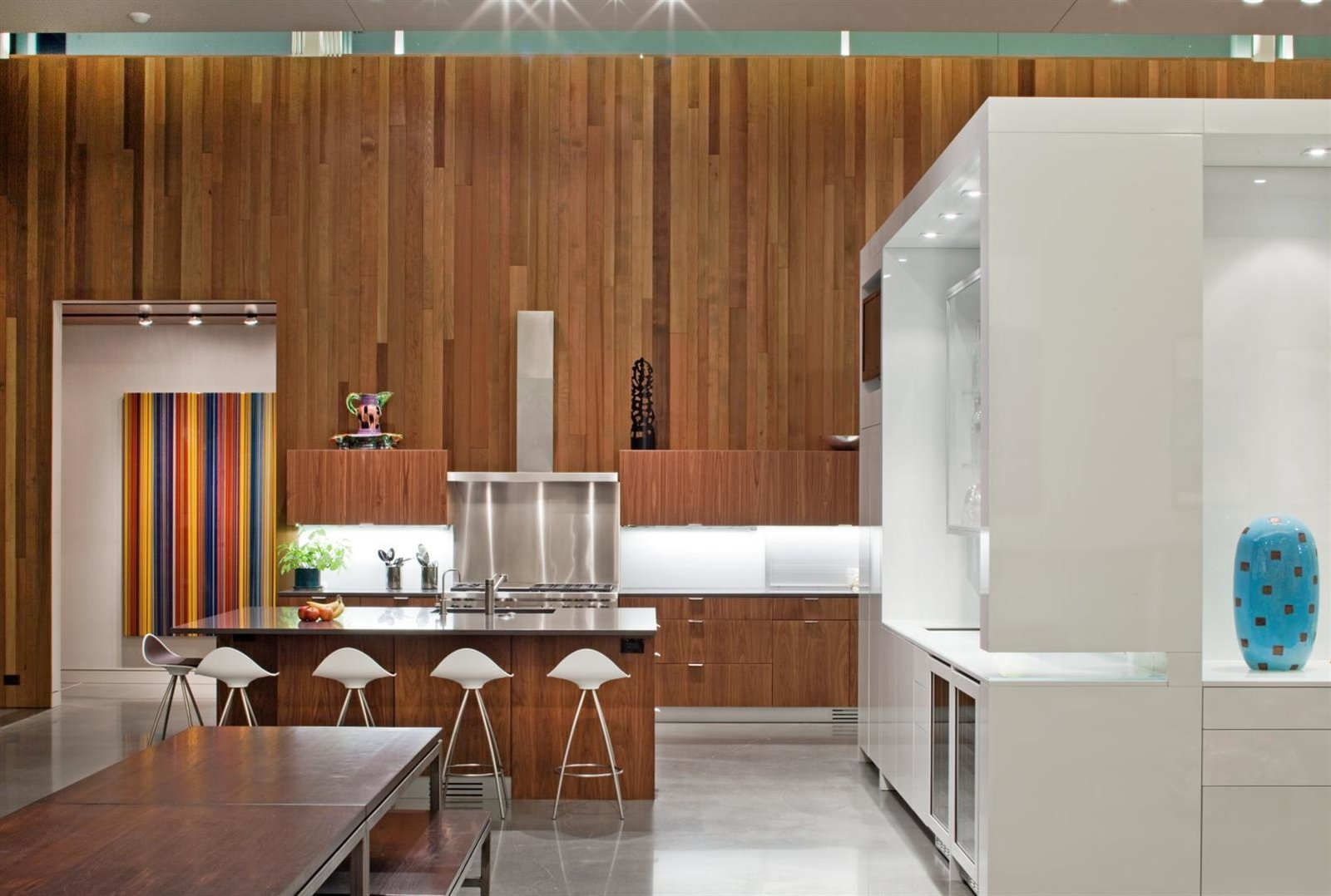 "The house features 16-foot-high ceilings and is heated and cooled primarily from geothermal ground loops, with radiant lines inside the concrete floors. A central ""cube"" designed and fabricated by the architects offers pantry storage and delineates the kitchen, living, and bar areas. The glossy sheen comes courtesy of white automotive paint."