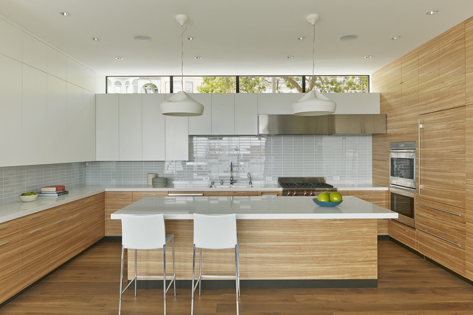 The architects wanted to create as much of a buffer as possible against the urban traffic outside the kitchen. A clerestory window manages to maintain a visual connection with the neighborhood while blocking its noise. The kitchen features Pleat Box pendant lights from Marset and Lio Stools by Roberto Barbieri for Zanotta. Tagged: Kitchen, Engineered Quartz Counter, White Cabinet, Medium Hardwood Floor, Glass Tile Backsplashe, Recessed Lighting, Pendant Lighting, Wall Oven, Range, and Range Hood.  Noe Residence by Caroline Wallis