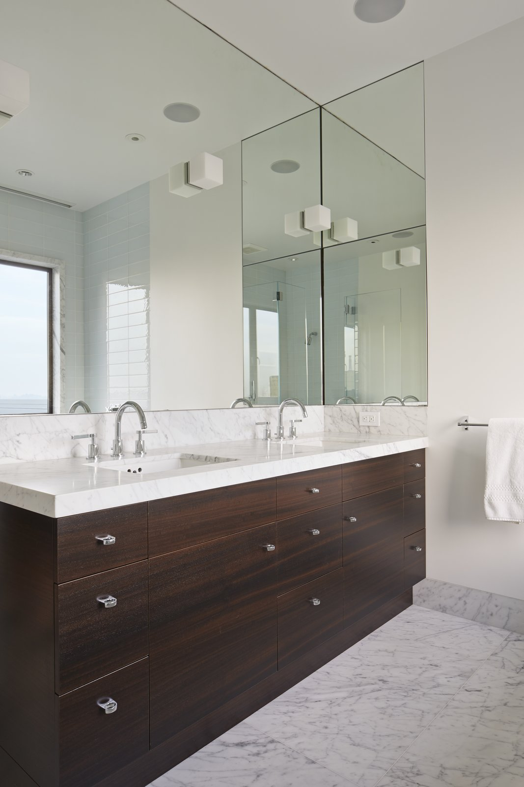 The clean symmetry of the master bathroom is enhanced by Ann Sacks ceramic Savoy tiles and Lefroy Brooks fixtures. Tagged: Bath Room, Marble Counter, Marble Floor, Undermount Sink, and Accent Lighting.  Noe Residence by Caroline Wallis