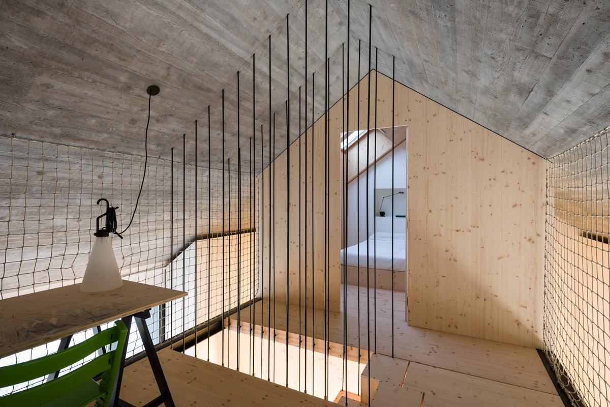 Steel rods surround the staircase. A MayDay lamp by Konstanting Grcic for Flos is affixed to the rope wall.