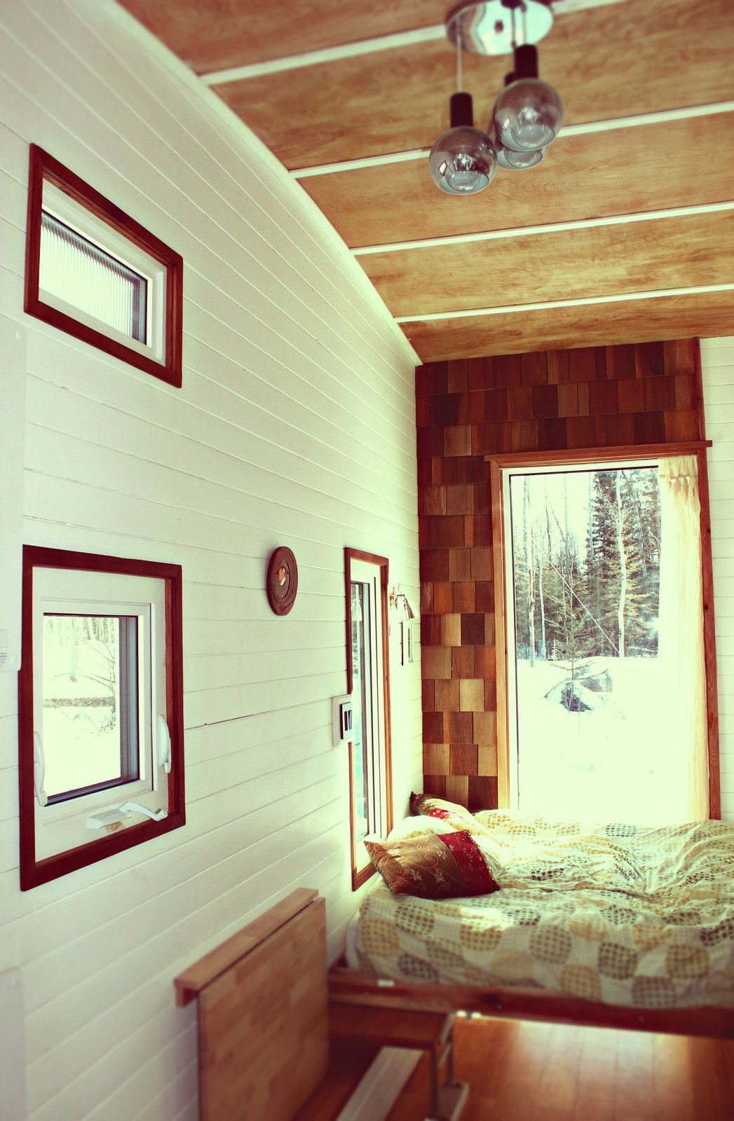 A custom Murphy bed occupies the rear end of the trailer, next to a wall of cedar shingles. The wall at left, which Herbert painted white, is tongue-and-groove pine.