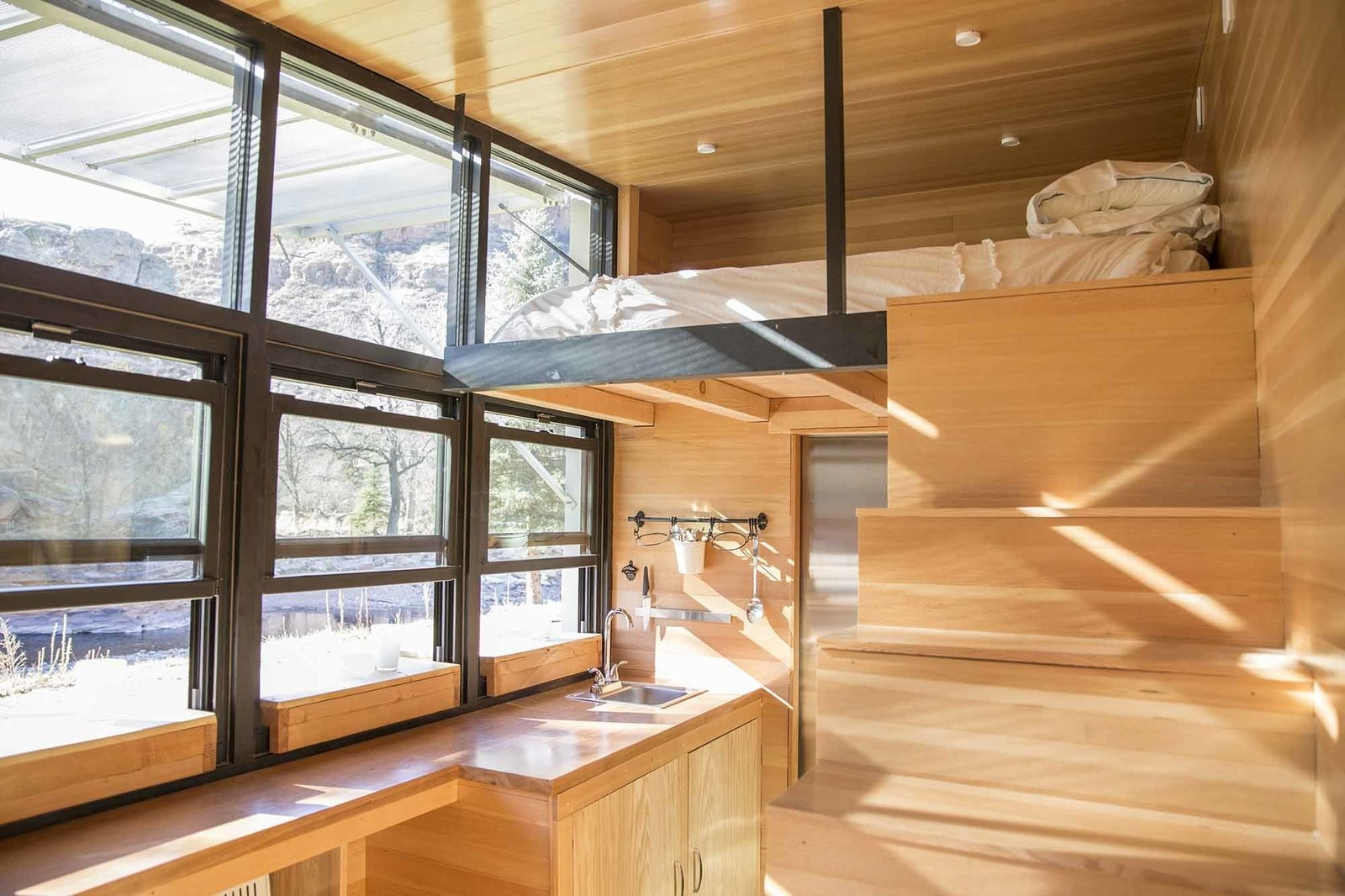 With a built-in sofa and sleeping loft, ATLAS can accommodate three adult travelers. Tagged: Kitchen, Wood Counter, and Wood Cabinet.  Clever Loft Spaces for Small Places by Diana Budds from A Tiny Trailer Home Harvests Solar Power and Rainwater to Save Energy