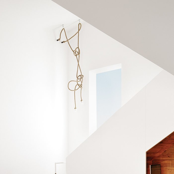 The stairway chandelier is made from designer Christien Meindertsma's flax-rope lamps for Thomas Eyck, which feature the same material as those used in Dutch shipping yards. At eight months pregnant, in anticipation of the new baby, Suttles mounted a ladder to arrange the rope, which her stepmother strategically sewed to achieve just the right shape. Tagged: Staircase.  Photo 10 of 12 in 1920s Bungalow Plus Modern Addition Equals Perfect Austin Home