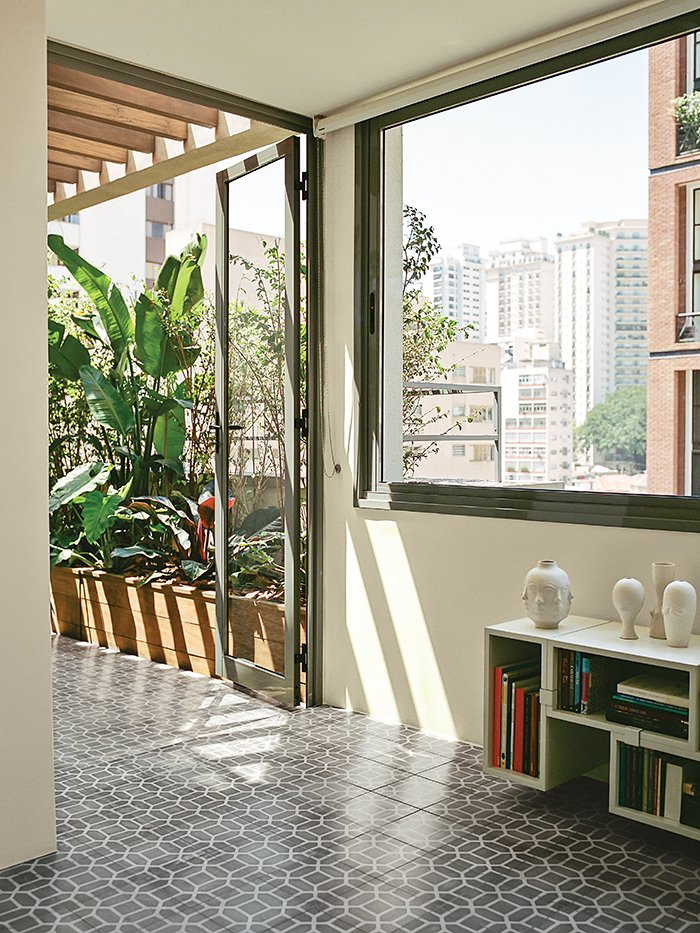 A Muuto Stacked shelf system hugs the wall beneath the window in the dining room. Tagged: Living Room, Storage, Shelves, and Bookcase.  Photo 9 of 15 in Amazing Garden Oasis in São Paulo Born from a Five-Year Search and Renovation
