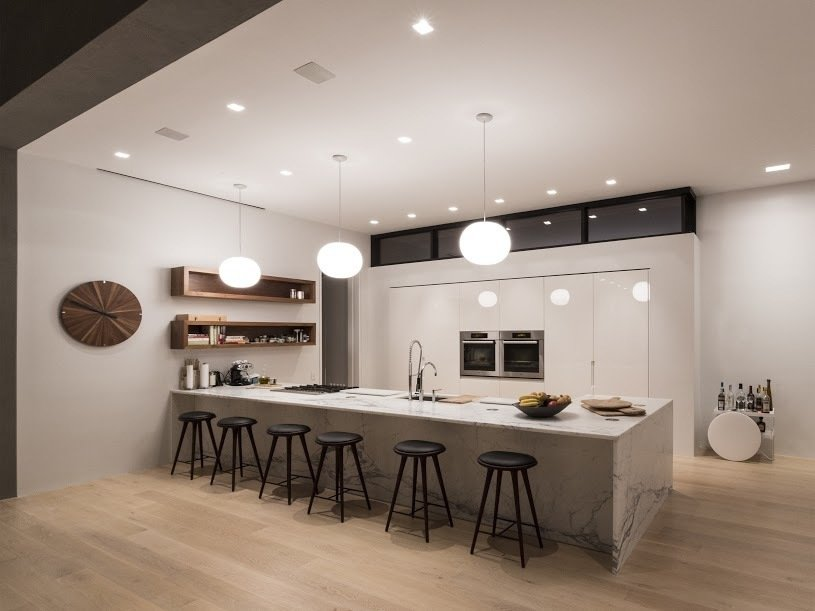 The minimalist kitchen features an array of lighting: can lights integrated into the ceiling as well as pendants.