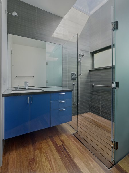 A custom skylight floods the bathroom with light. A tempered glass shower and Grohe faucet accent the space; custom glossy cabinetry with Hafele hardware again adds a pop of color.