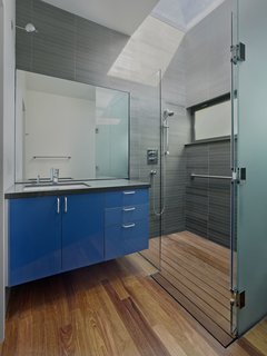 An Indoor-Outdoor Renovation for a 1950s Ranch House in the Bay Area - Photo 6 of 8 - A custom skylight floods the bathroom with light. A tempered glass shower and Grohe faucet accent the space; custom glossy cabinetry with Hafele hardware again adds a pop of color.