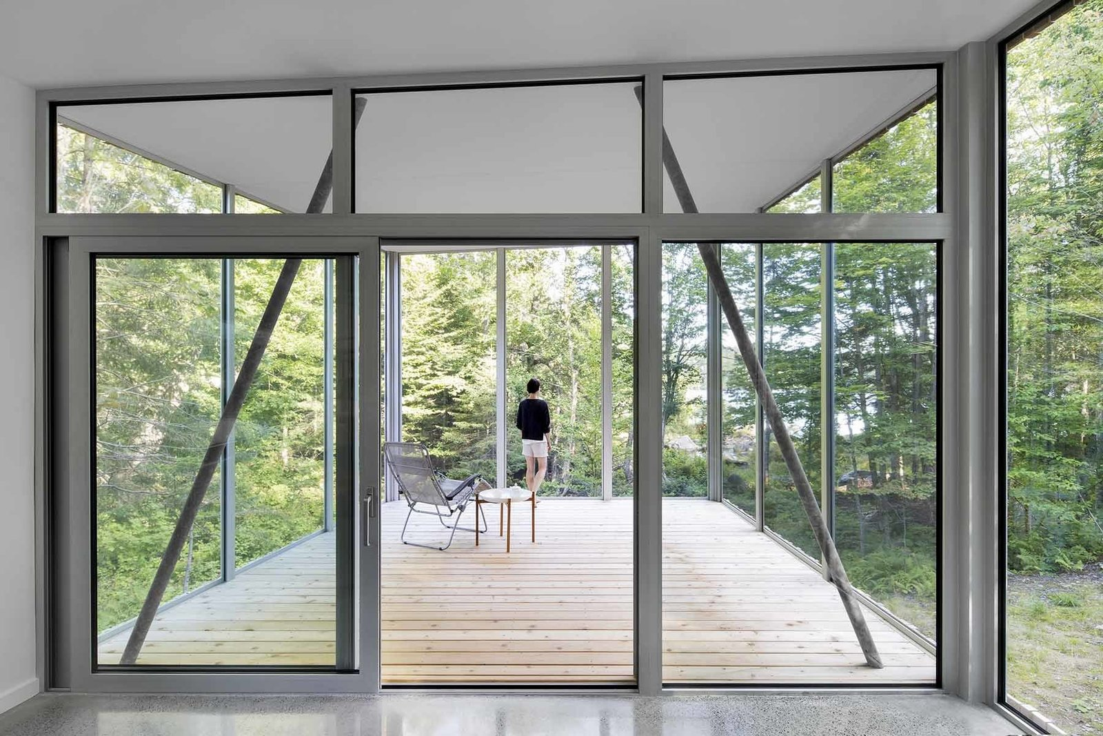 Large aluminum windows by Alumilex offer striking views while taking advantage of the sun's orientation. In the summer, the leafy trees help shield the house from heat. During cooler months, sunlight filters through bare tree branches to flood the home with warmth and light.  House of Lake Grenier by Tiffany Jow