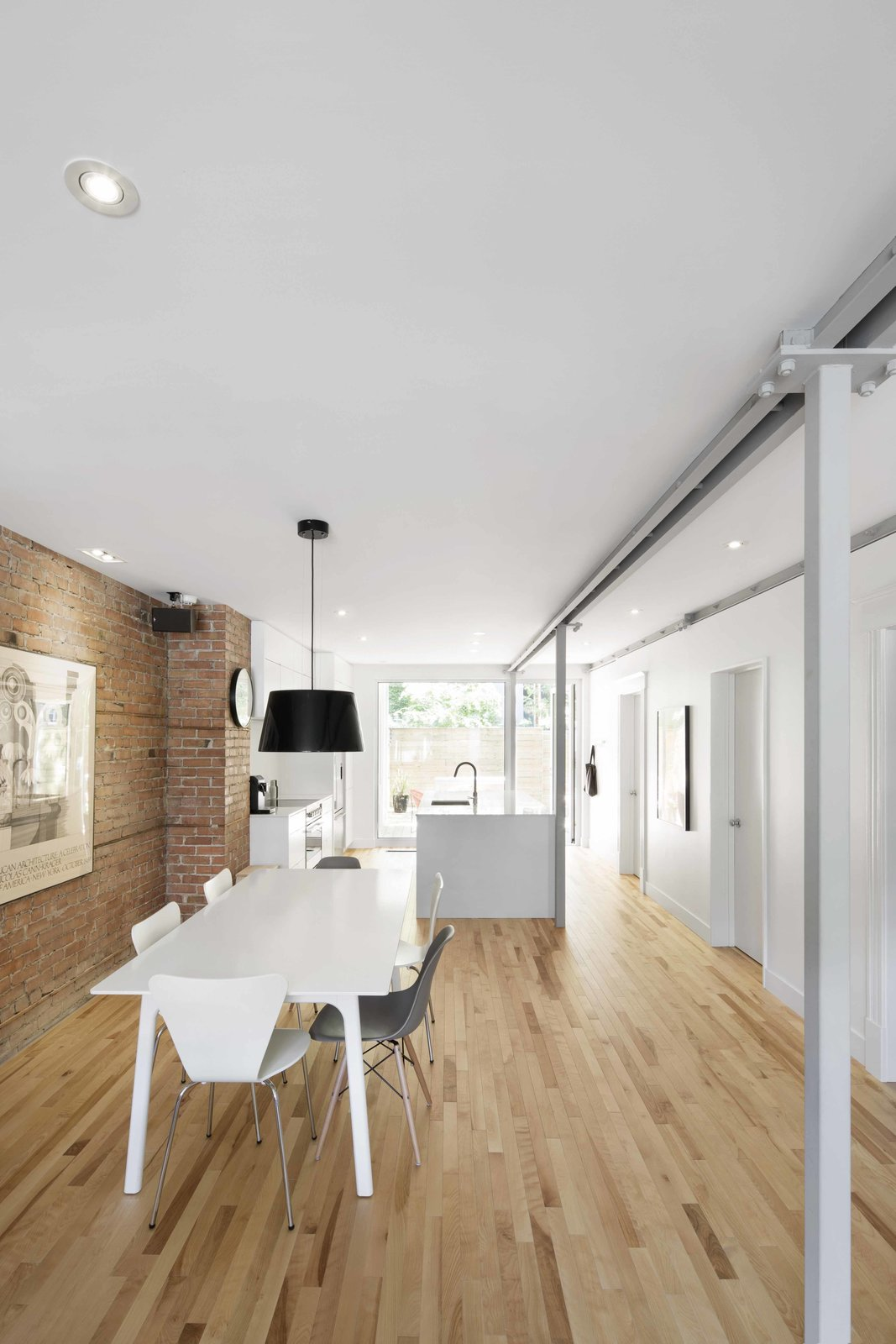 A linear layout allows for air and light to flow freely through the apartment, making it an a open haven in the center of the city. An IKEA pendant and chairs surround a table by Zone Maison.  Photo 6 of 8 in Blocked in on Two Sides, a Renovation Opens a Quebec Apartment to Tons of Natural Light